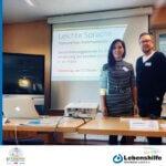 Masa Ahmadi und Michael Bach stehen beim Fachtag vor einer PowerPoint-Präsentation.